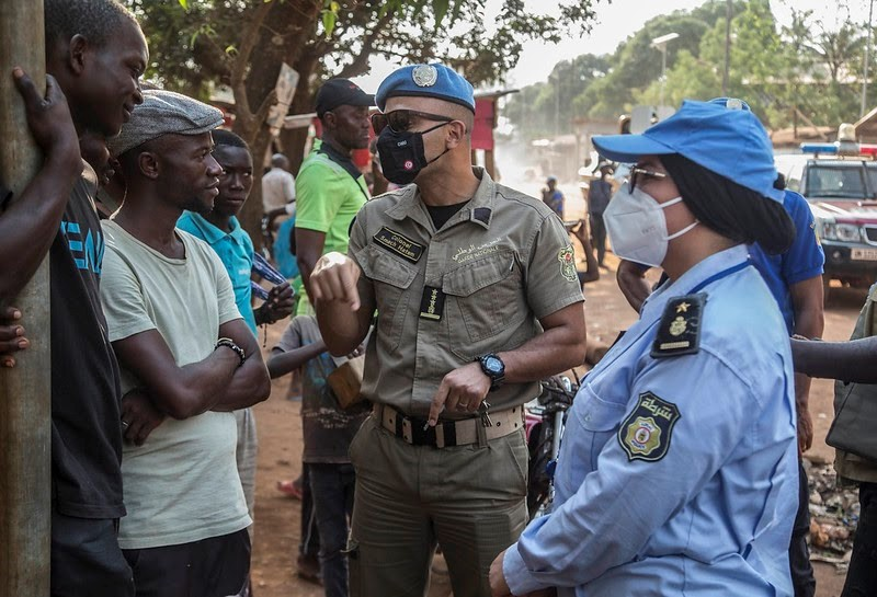 During a security patrol in Bangui, Central African Republic, two United Nations Police peacekeepers discuss safety and security with local youth. Photo by: MINUSCA
