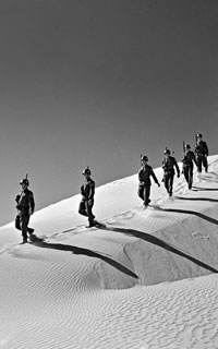 Peacekeepers walking in single file down a sand dune.