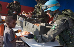 A peacekeeper serving food to a young boy.