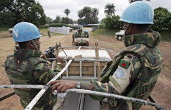 Two peacekeepers riding on the top of a truck driving down a dirt road.