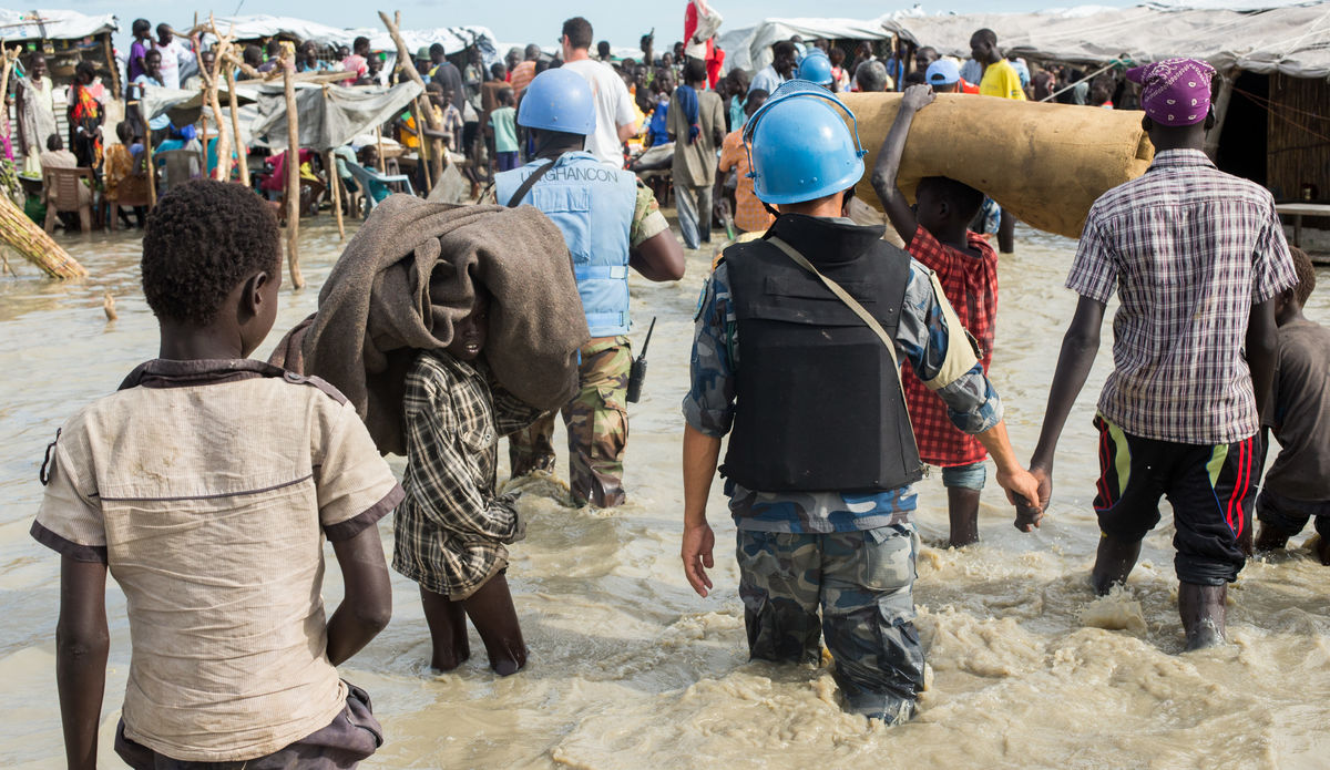 Displaced people living in flooded protection site.