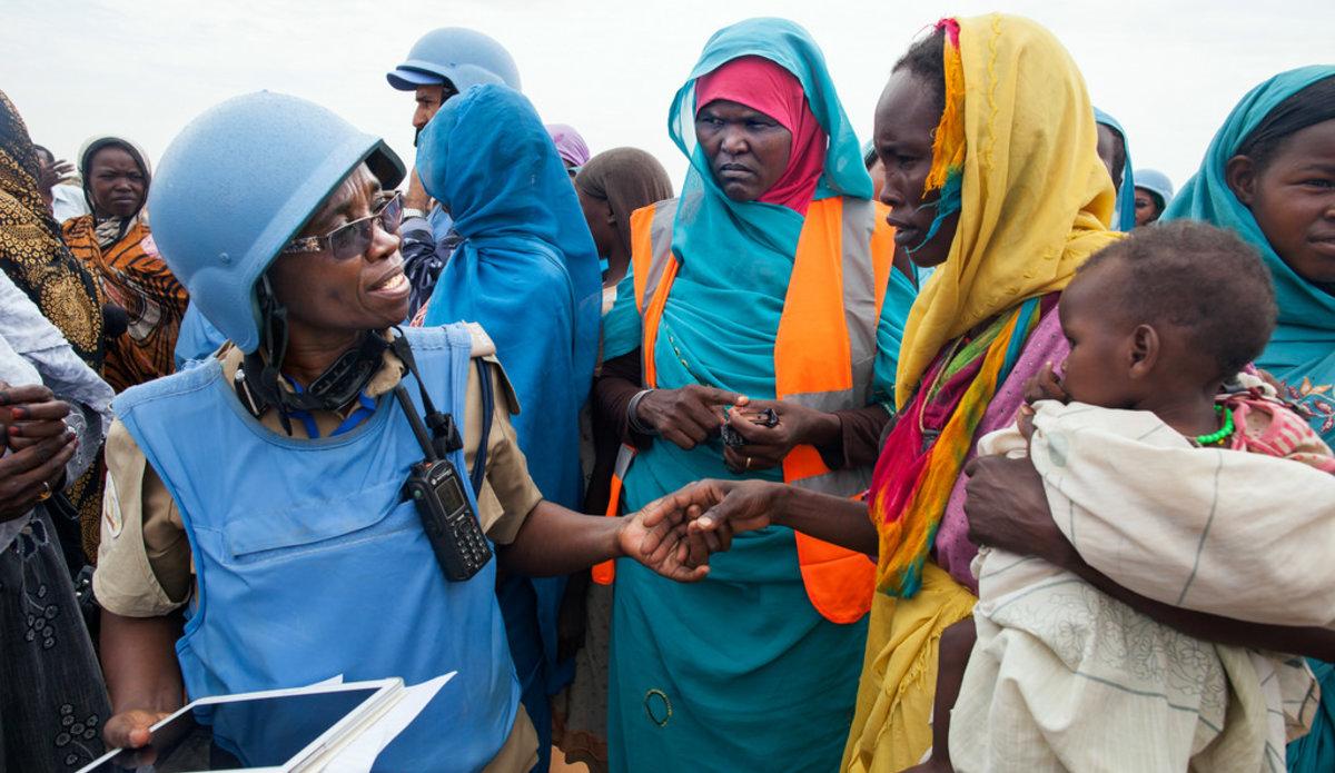 ضابطه شرطية في العملية المختلطة غرايس نغاسا (من تنزانيا) والمتطوعة   ، جزيرة أحمد محمد ، في حوار تفاعلي مع امرأة في مخيم زمزم للمشردين ، شمال دارفور. الصورة: ألبرت غونزاليس فران / يوناميد