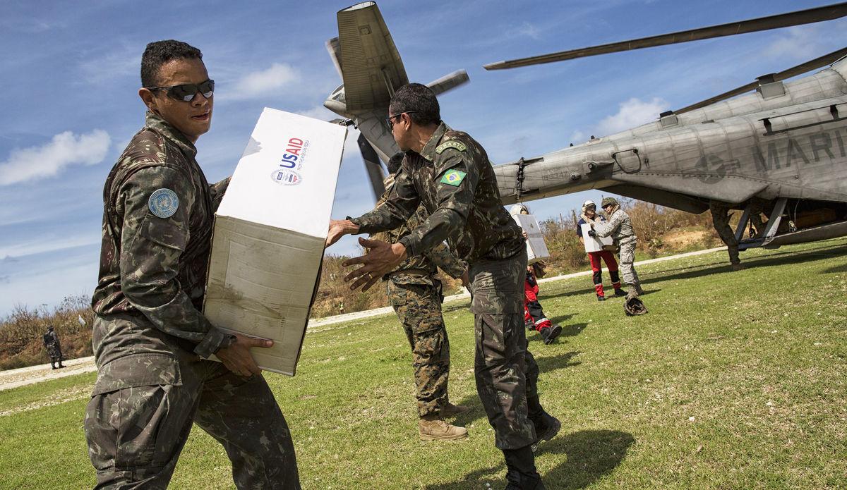Des Casques bleus brésiliens de la Mission des Nations Unies en Haïti (MINUSTAH) aident à décharger un hélicoptère militaire de ravitaillement.