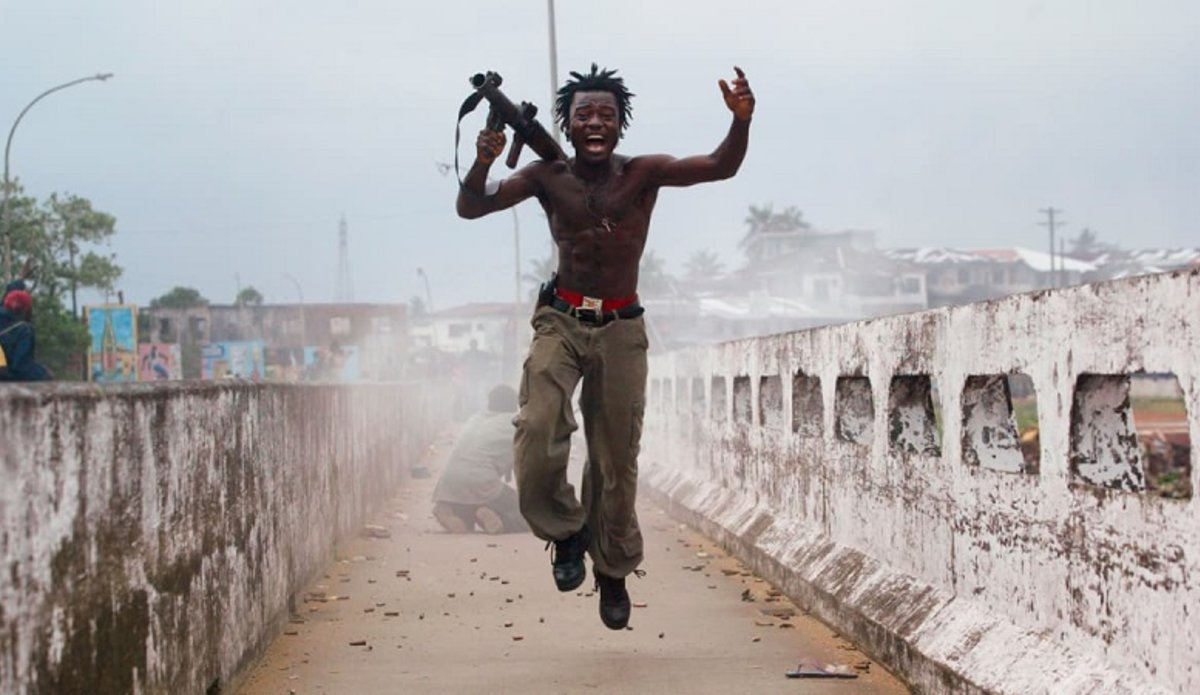 Командир группы либерийских ополченцев торжествует, запустив реактивную гранату по силам повстанцев на стратегически важном мосту в Монровии, 20 июля 2003 года. Фото: Крис Ондрос